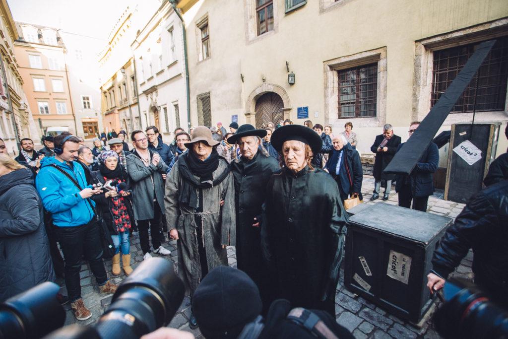 Zdjęcie przestawiające aktorów Teatru Cricot 2, którzy przebrani w kostiumy odgrywają tak zwane Żywe Pomniki 8 grudnia.