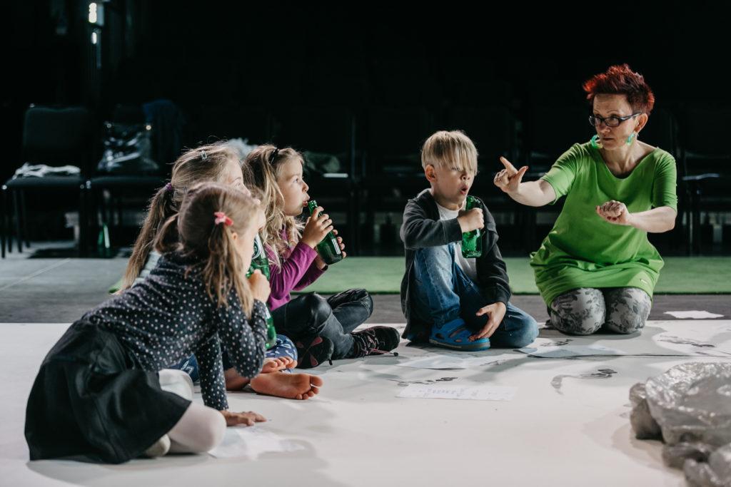 Na zdjęciu grupa dzieci dmuchająca w butelki i dyrygentka. Fot. Studio FILMLOVE