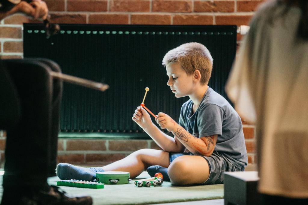 Na zdjęciu chłopiec grający pałeczkami na różnych instrumentach. Fot. Studio FILMLOVE