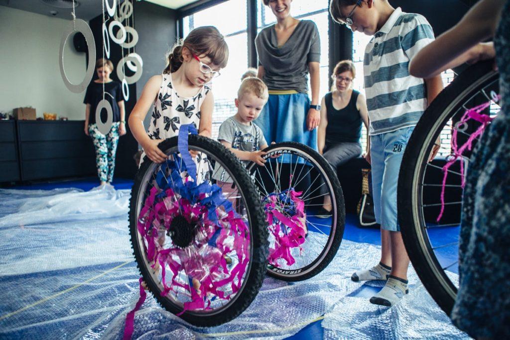 Na zdjęciu grupa dzieci bawi się kołami rowerowymi. Fot. Studio FILMLOVE