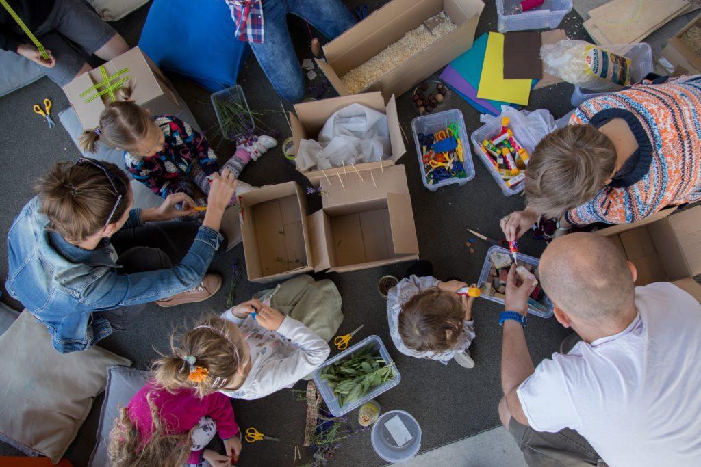 Na zdjęciu grupa dorosłych i dzieci pracująca z nożyczkami, klejem i kartonami.  Fot. Studio FILMLOVE