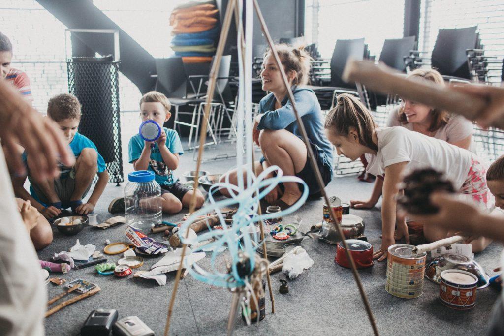 Dzieci i prowadząca w otoczeniu patyczków, z których powstają budowle.