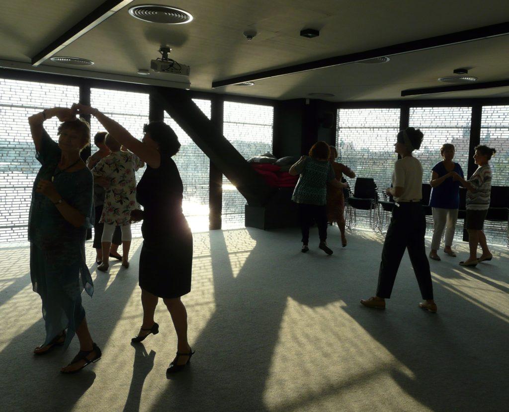 Zdjęcie przedstawia tańczących seniorów. W tle widok na Wisłę.