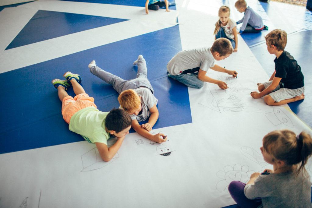 Dzieci rysują na dużych arkuszach papieru.