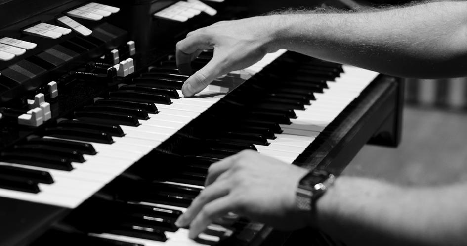 Zdjęcie przedstawia ręce ułożone na klawiszach fortepianu.
