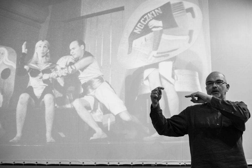 Na czarno białym zdjęciu Dariusz Kosiński wygłasza wykład, w tle zdjęcia ze spektaklu