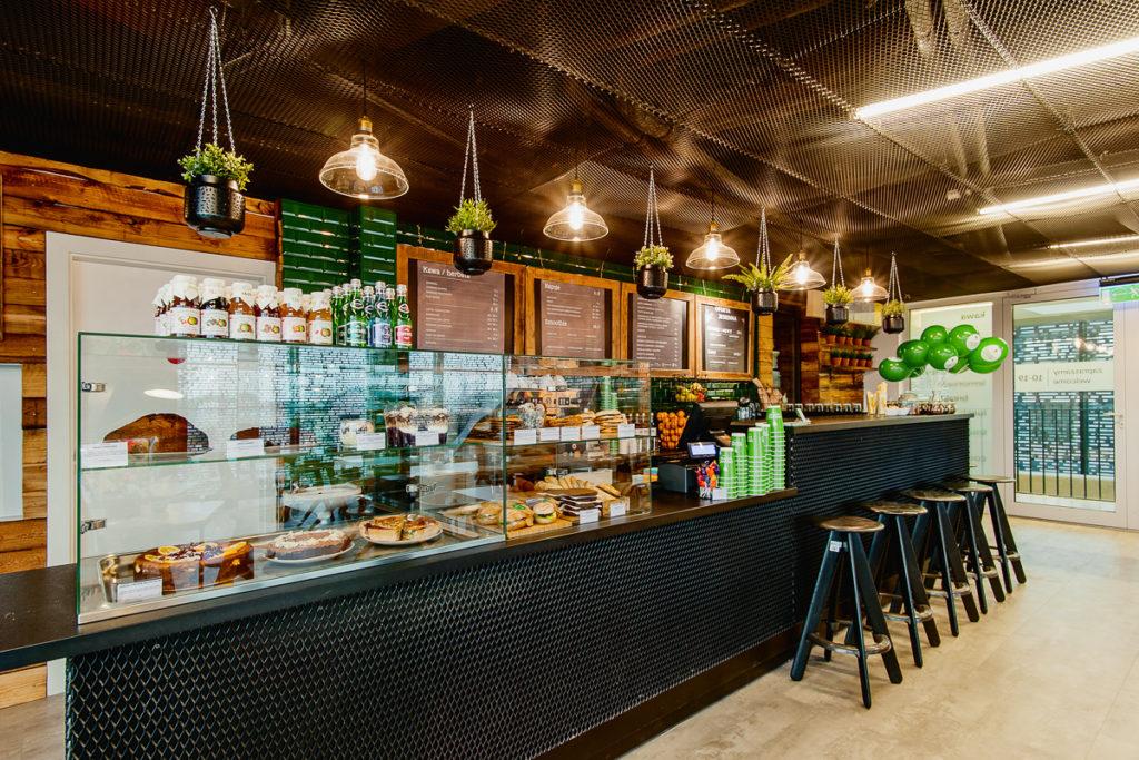 Widok baru w kawiarni w Cricotece. Stołki barowe, bar oraz witryna z potrawami