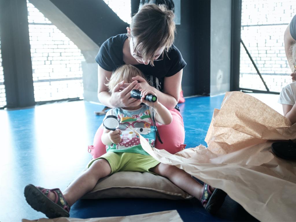 Na zdjęciu dziecko siedzi na podłodze, przykłada latarkę do twarzy. Dorosły zasłania mu oczy.