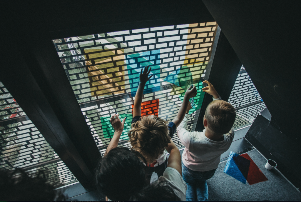 Na zdjęciu dwoje dzieci i dorosły przykładają do szyby okiennej kolorowe folie.