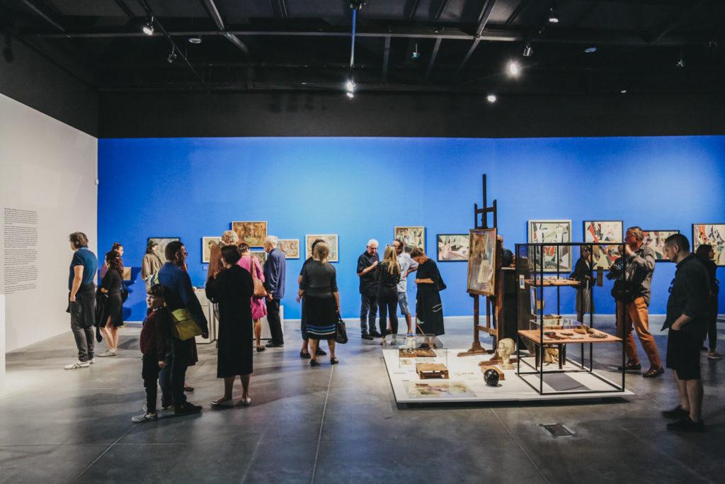 Zdjęcie: widzowie zwiedzają wystawę Jaremianki. Kadr skierowany jest na bibeloty z pracowni artystki i przeglądające je osoby stojące na tle obrazów.
