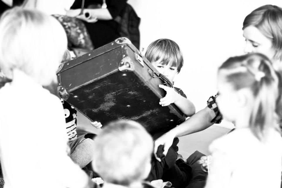 Na czarno-białym zdjęciu dzieci trzymają walizkę