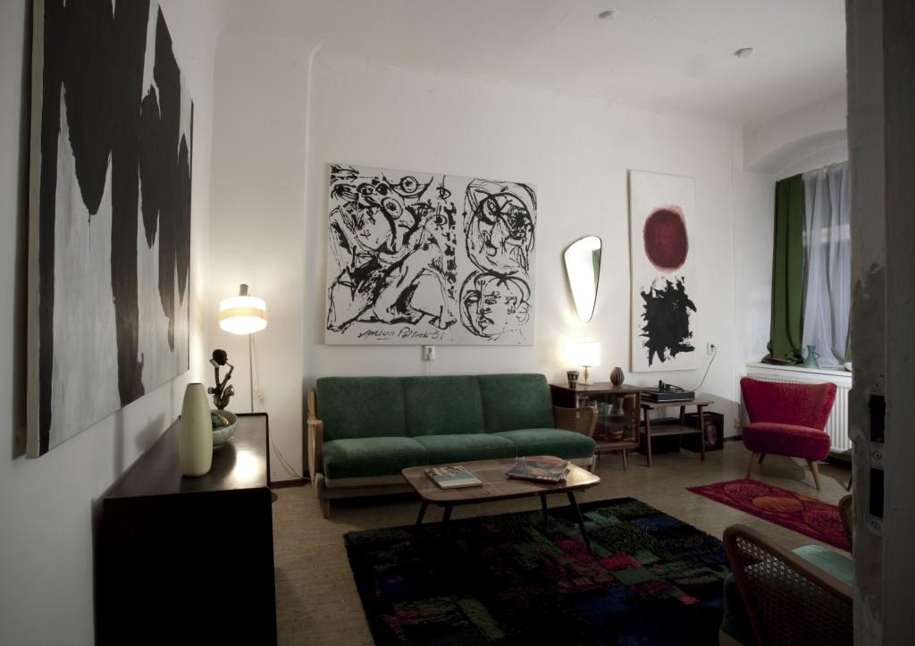 [Wnętrze eleganckiego pokoju, na ścianach wiszą abstrakcyjne obrazy]