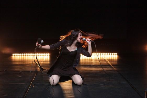 Kobieta śpiewa do mikrofonu. Klęczy na scenie z rozwianymi włosami.