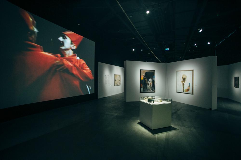 Wnętrze wystawy, na ściankach działowych wiszą obrazy, na ścianie wyświetla się obraz dwóch tańczących mężczyzn