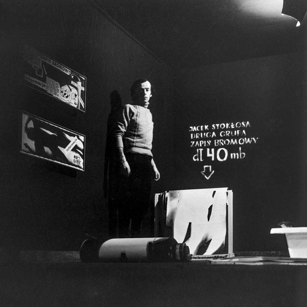 Zdjęcie mężczyzny w ciemnym pomieszczeniu, w tle napis Jacek Stokłosa Druga Grupa zapis bromowy