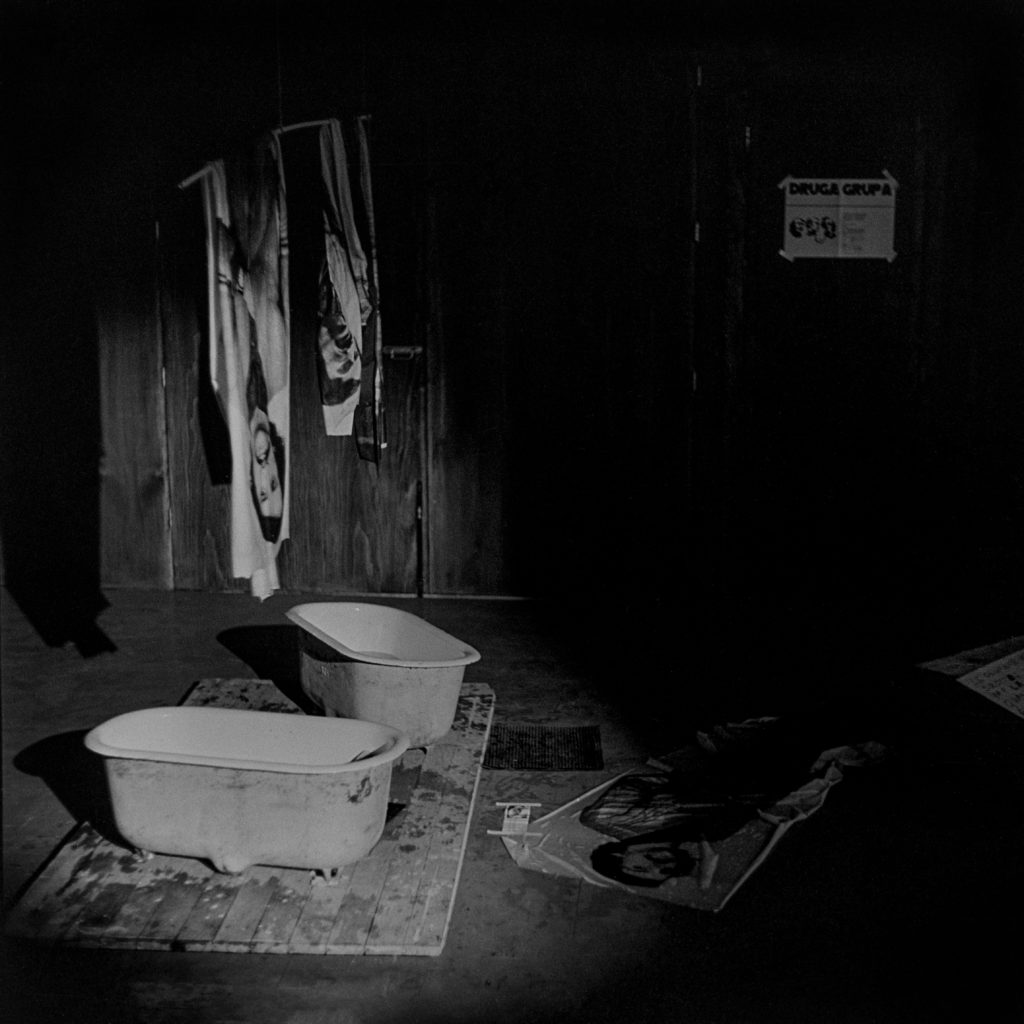 Archiwalne zdjęcie; wnętrze ciemnego pomieszczenia, na podłodze stoją małe wanienki do których skapuje woda z dużych odbitek