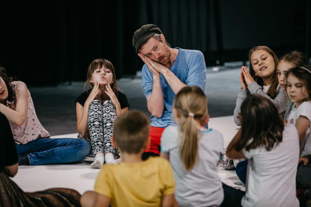 Mężczyzna i grupa dzieci siedzą w kółku; wszyscy przykładają ręce do policzka w geście udającym sen