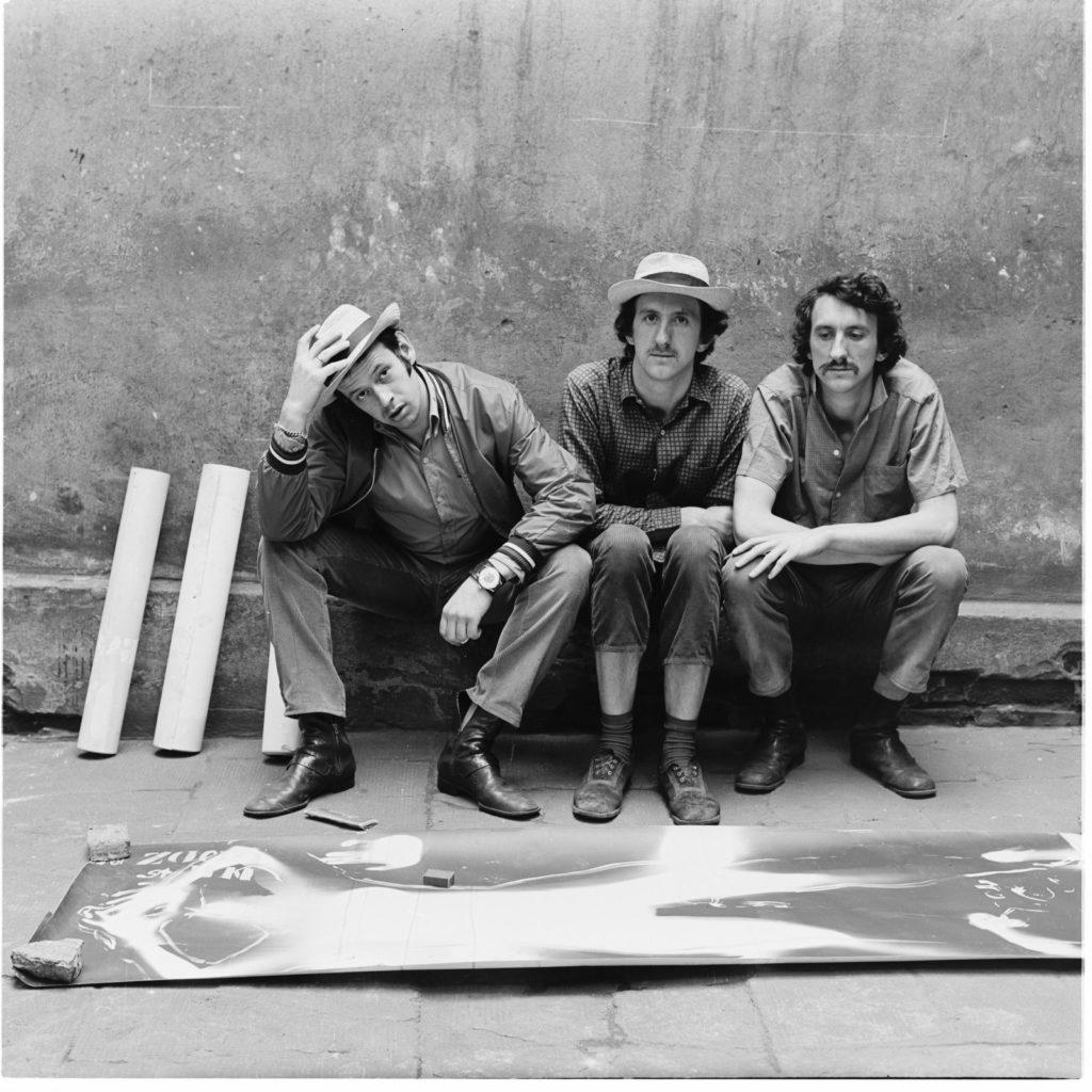 3 mężczyzn siedzących na murku; przed nimi na ziemi leży element wystawy
