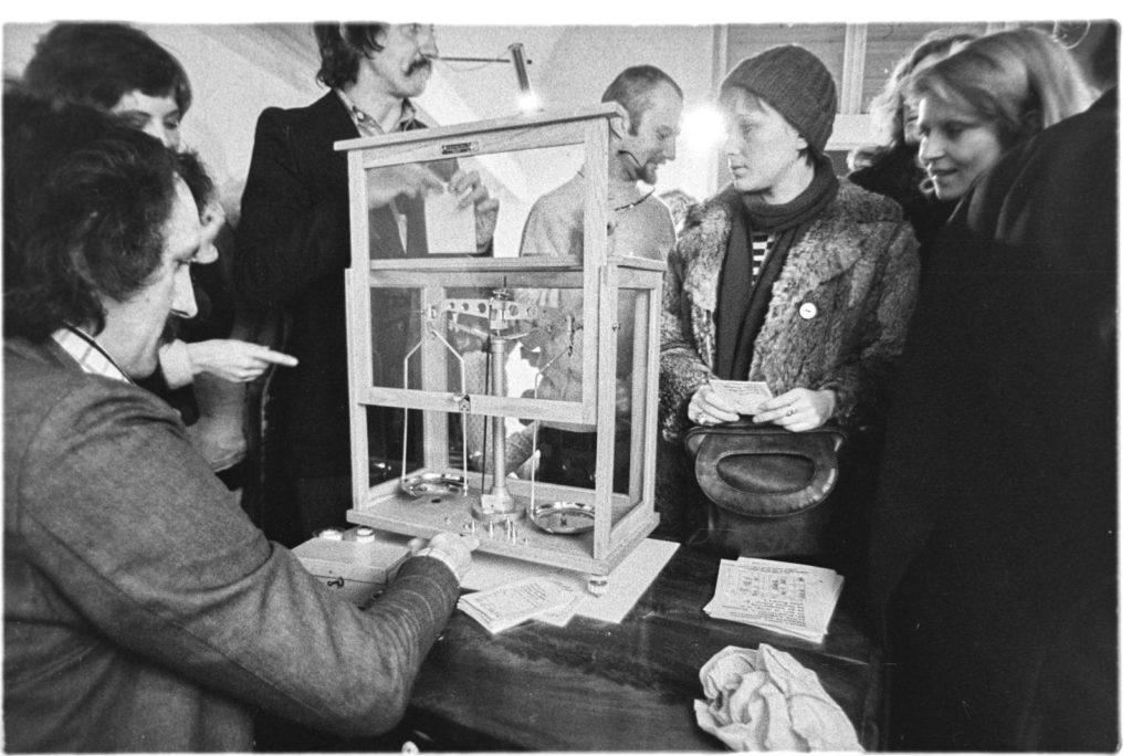 Archiwalne zdjęcie; grupa osób stoi nad mężczyzną siedzącym przy biurku z małą wagą.