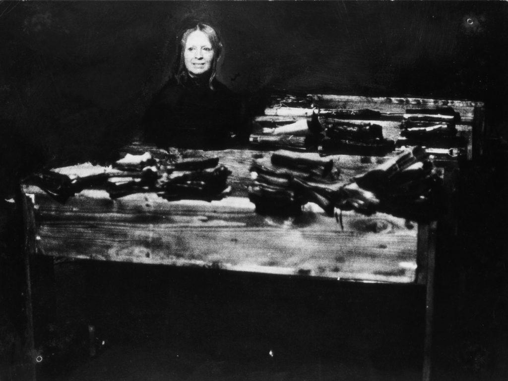 Na zdjęciu kobieta w czarnym ubraniu w ławce szkolnej