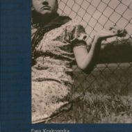 Okładka ze zdjęciem kobiety siedzącej pod drucianą siatką