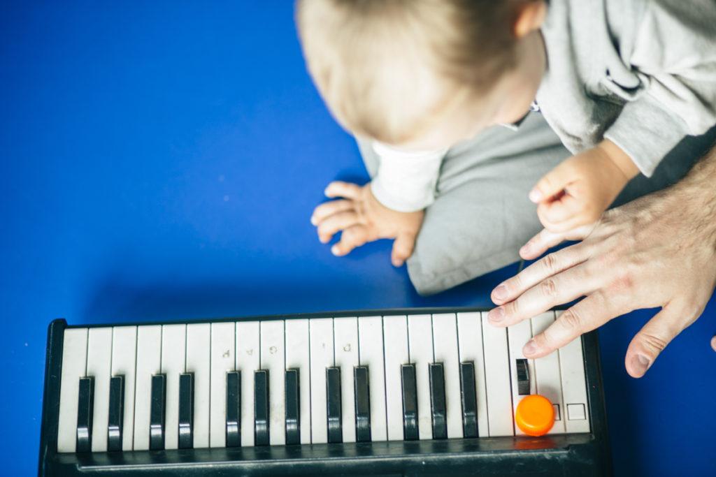 Na zdjęciu dziecko i ręka osoby dorosłej uderzająca w klawisze instrumentu. Fot. Studio FILMLOVE