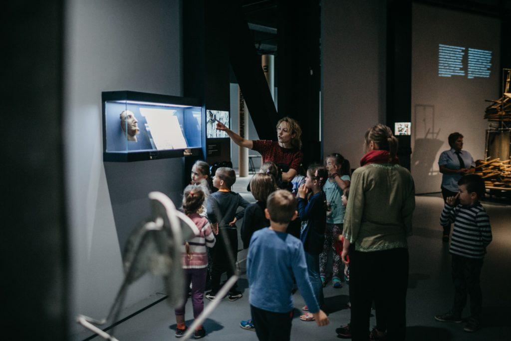 Na zdjęciu grupa na wystawie. Przewodniczka pokazuje obiekt. Fot. Studio FILMLOVE