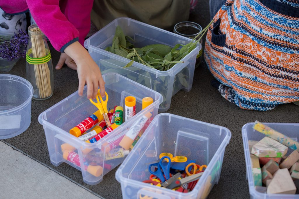 Na zdjęciu ręka dziecka sięgająca po nożyczki z plastikowego pudełka. Fot. Studio FILMLOVE
