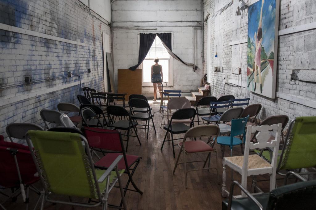 Postać stoi przed odsłoniętym oknem w sali pełnej pustych krzeseł