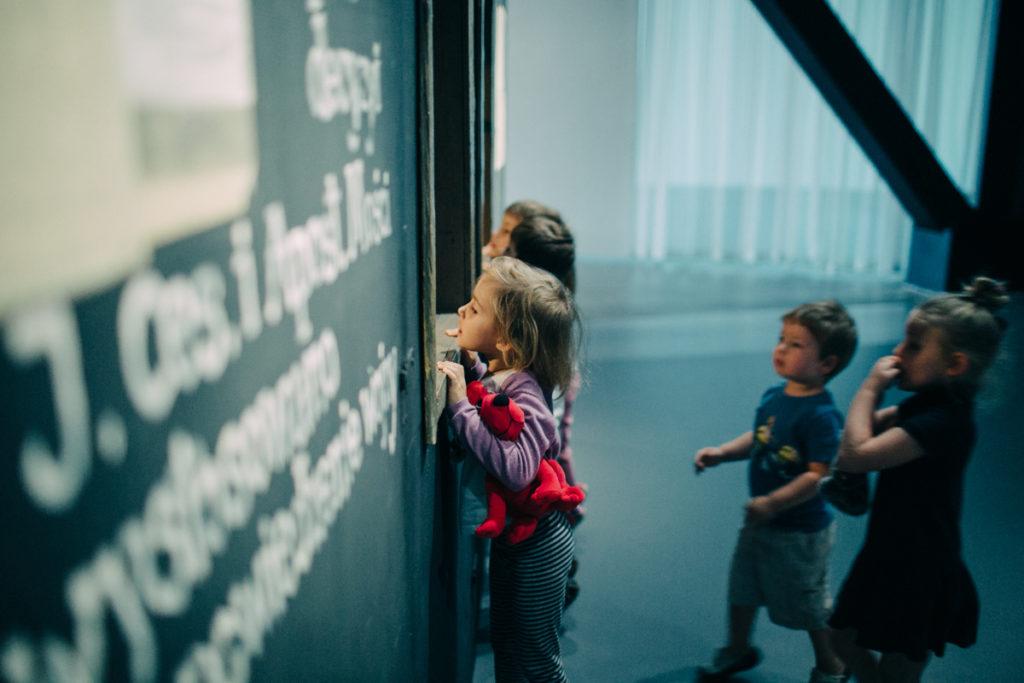 Fotografia przedstawiająca dzieci zaglądające przez okna.