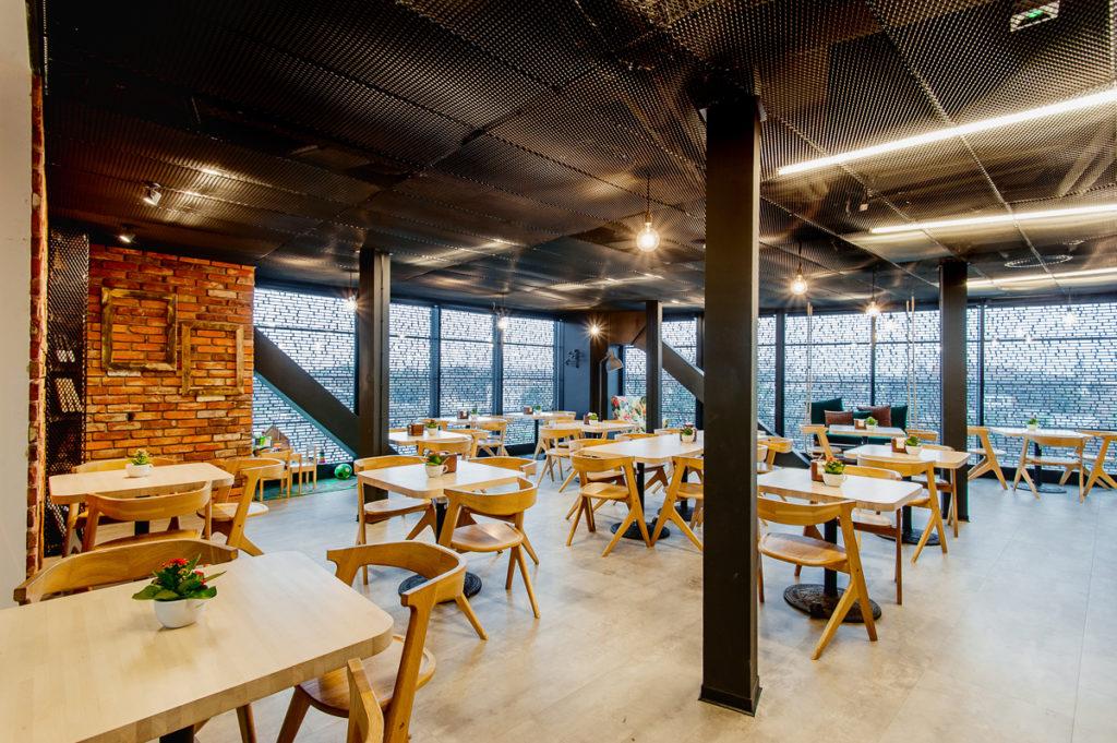 Wnętrze kawiarni w Cricotece. Widać ustawione stoliki w tle widok na Wisłę