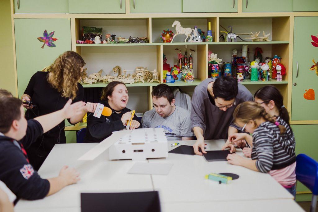 Zdjęcie z warsztatów scenograficznych. Widać na nim uczestników warsztatów oraz eukatorkę udzielającą rad.