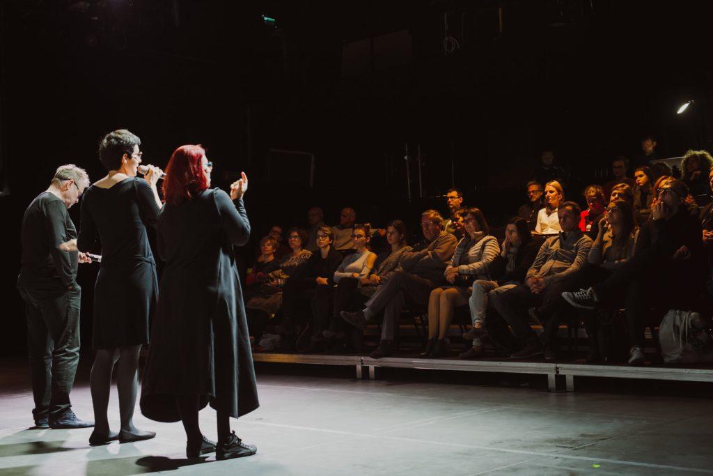 Na zdjęciu widać ludzi siedzących na sali teatralnej, naprzeciwko nich stoją moderatorzy spotkania.