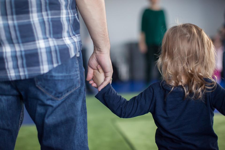 Dorosły człowiek i dziecko trzymają się za ręce