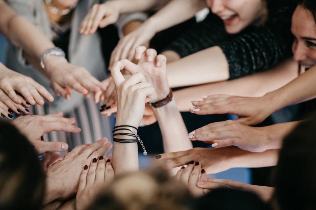 Na zdjęciu widać ręce grupy uczestników warsztatów, które są uniesione i układają się w krąg