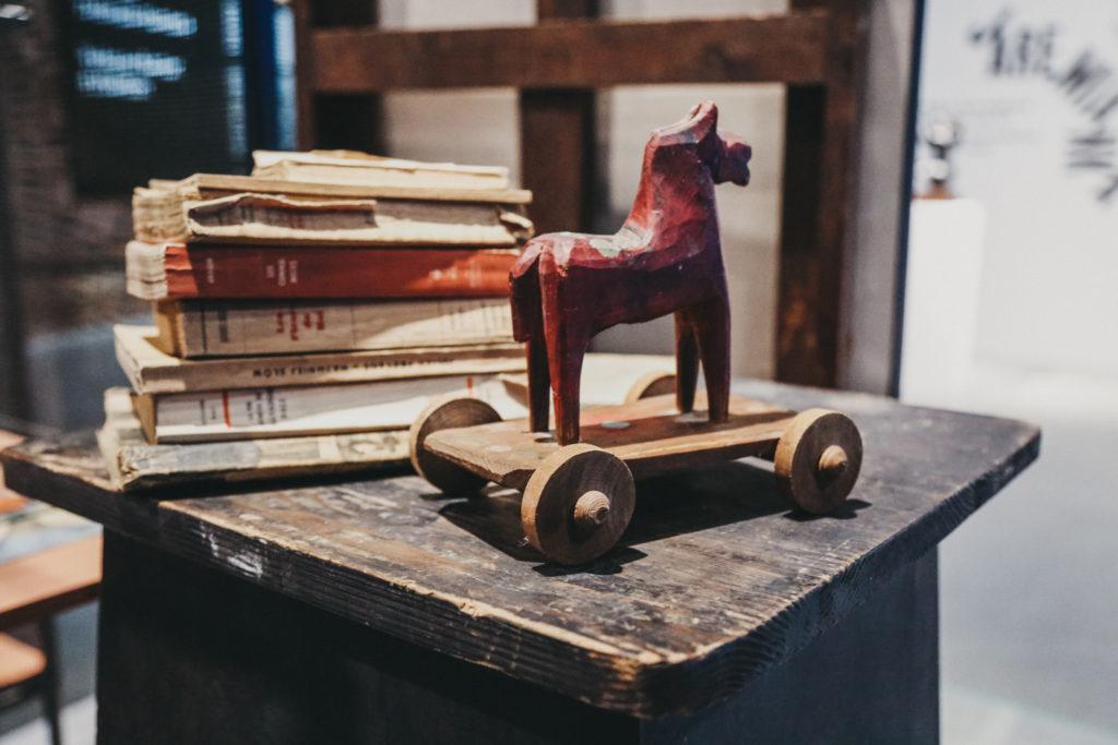 Na zdjęciu widać drewnianego konika ustawionego na podeście. W tle ułożone w stosik książki
