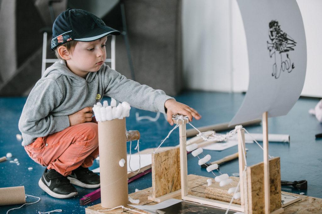 Na zdjęciu chłopiec kuca obok drewnianej konstrukcji przypominającej statek.