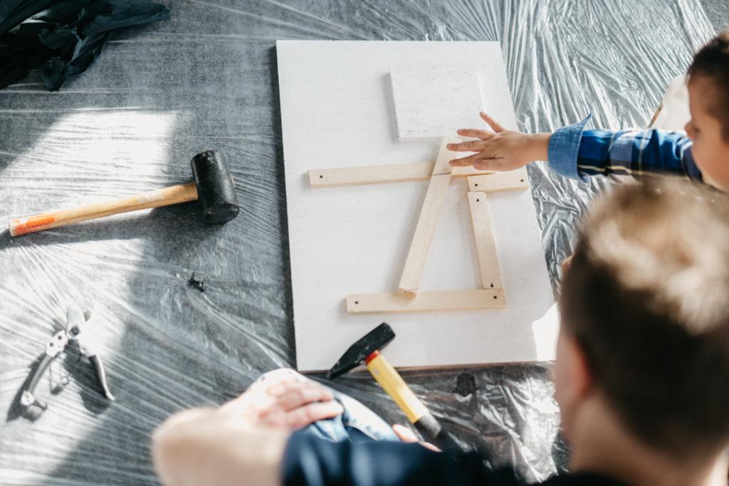 Na zdjęciu konstrukcja z listewek ułożonych na desce obok narzędzia oraz dziecko z rodzicem.