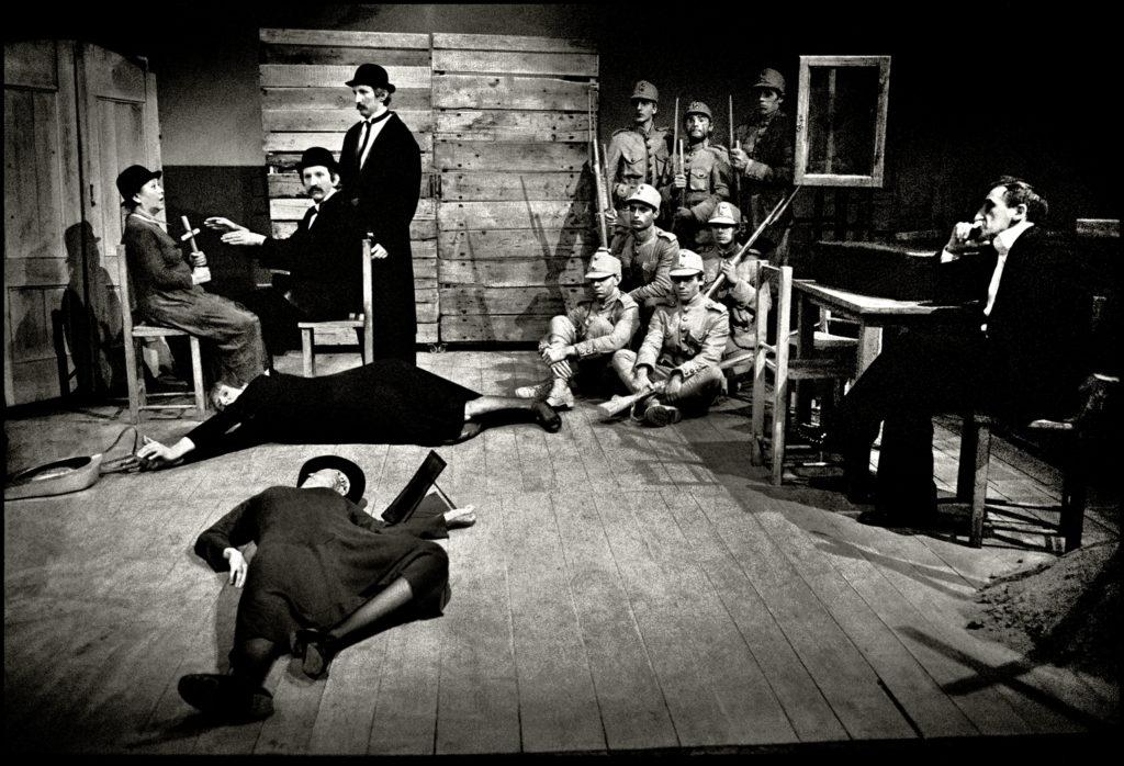 Czarno-biała fotografia przedstawia scenę ze spektaklu. Z prawej strony Tadeusz Kantor siedzi przy stole. W głębi grupa żołnierzy ustawiona jak do pamiątkowego zdjęcia. Z lewej strony aktorzy siedzą na krzesłach. Przed nimi na drewnianej podłodze leżą dwie osoby w dziwnych pozach.