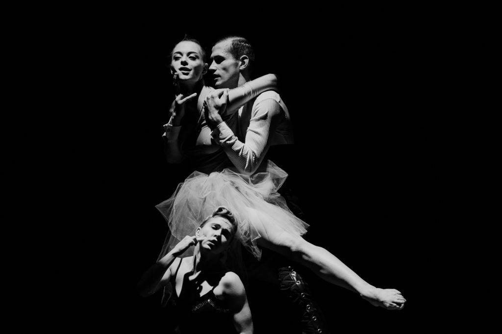 Na czarno-białej fotografii widsać trójkę tancerzy: dwie kobiety, jednego mężczyznę