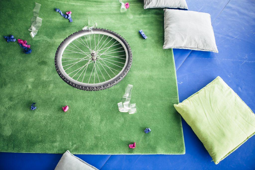 Na zdjęciu zielony dywan, na którym leżą rozrzucone koło od roweru, kawałki kolorowej bibuły i celofanu. Obok na niebieskiej podłodze poduszki.