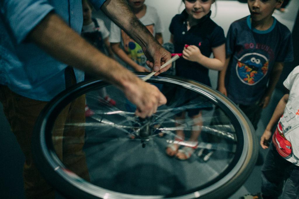 Na zdjęciu: Dzieci patrzą na koło rowerowe w ruchu