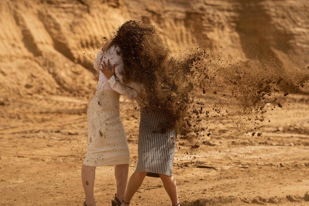 Na zdjęciu widać dwie przytulone kobiety zasłaniające się przed piaskiem.