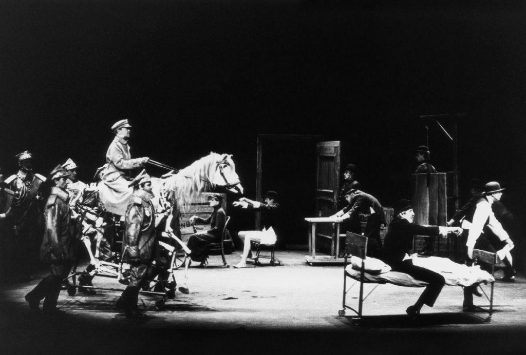 Czarno-biała fotografia przedstawia scenę ze spektaklu. Z lewej strony postacie w mundurach generałów prowadzą szkielet konia. Na jego szczycie jedzie postać w żołnierskim mundurze. Z prawej strony na łóżku siedzi mężczyzna w meloniku – druga postać ciągnie łóżko za sobą. Dalej – jak po torze – ustawione są kolejne postacie siedzące na krzesłach lub przesuwające meble.