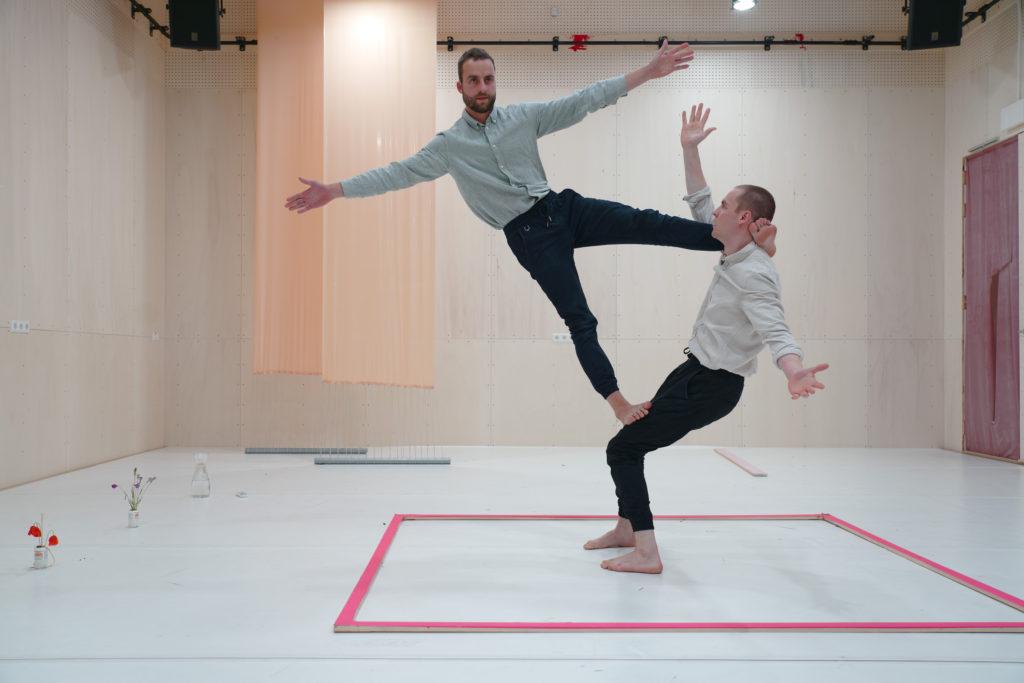 Zdjęcie: dwóch tancerzy, ubranych w czarne spodnie i jasne koszule, wykonuje układ: jeden stoi na ziemi z ugiętymi kolanami, drugi stoi jakby w powietrzu - jedną nogę ma opartą na udach partnera, drugą zaczepioną za jego głową. Obaj szeroko rozkładają ręce.