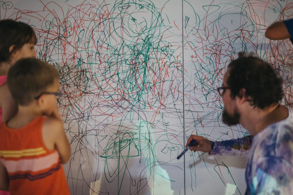 Na zdjęciu prowadzący wraz z dziećmi rysuje po podobraziu. Płótno pokryte jest gąszczem zielonych i czerwonych linii.