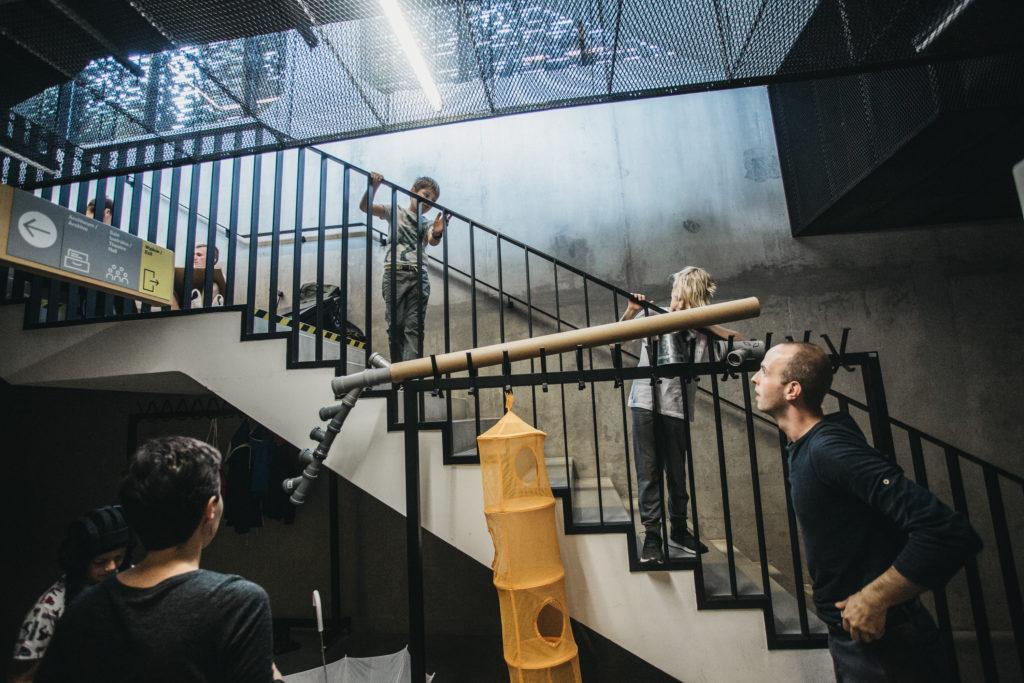 Zdjęcie na klatce schodowej. Dzieci stoją na schodach, spoglądają na ułożoną obok schodów konstrukcję z przedmiotów: rurek, wieszaków, parasoli. Obok prowadzący.