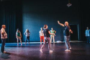 Uczestniczki i uczestnicy podczas ćwiczeń tanecznych na scenie Cricoteki