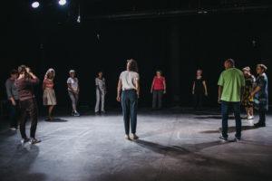 Stojąca w kręgu w sali teatralnej grupa kilkunastu osób w różnym wieku