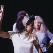 Kobieta w białej bluzce podnosi do góry dwa palce; w tle osoby się jej przyglądają